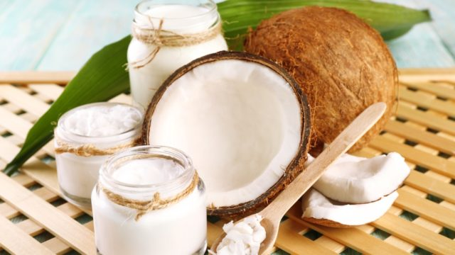 Fresh coconut oil in glassware on color wooden table and grid tray background